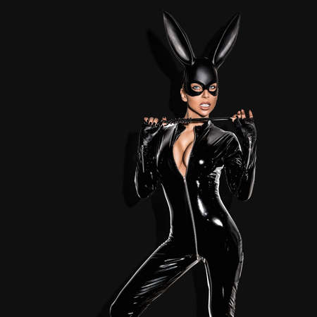 Sexy girl in Halloween costume. Sexy blonde woman posing in latex costume and black mask on black background. Halloween concept.