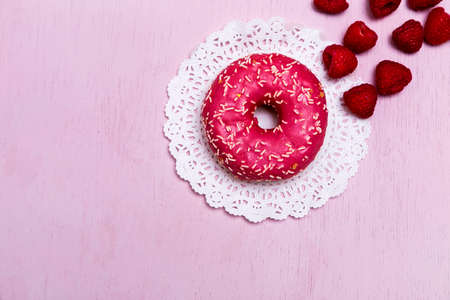 Donuts with icing on pastel pink background. Sweet donuts. Party food concept with copy space. Banner.
