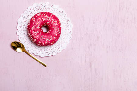 Donuts with icing on pastel pink background. Sweet donuts. Candies on wooden background. Party food concept with copy space. Banner. 免版税图像