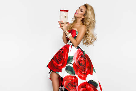 Beautiful blonde woman in an elegant evening dress with red roses, holds a present. Chrismas and valentines time. Female model with gift on a white background.