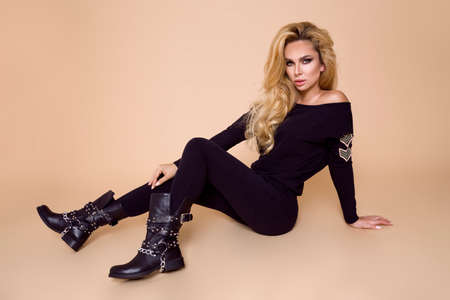 Beautiful, young female model in a autumn-winter clothing, military hoodie and overalls and boots on a beige background in the studio. Blonde in elegant biker, military style clothing