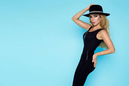 High fashion Model isolated on blue background. Beauty stylish blonde woman posing in fashionable clothes in studio. Casual style, beauty accessories. Sexy woman with hat.