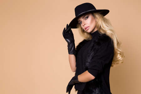 High fashion Model isolated on beige background. Beauty stylish blonde woman posing in fashionable clothes in studio. Elegant style, beauty accessories. Elegant wonan in Hat and gloves.