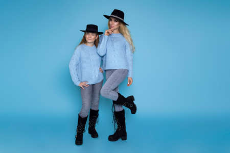 Portrait of beautiful blond girls, mother with her daughter in winter clothing on blue background.