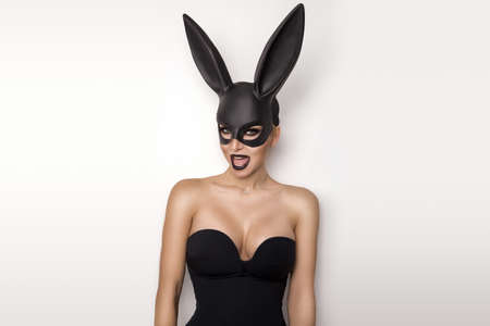 Sexy woman in a black bunny mask isolated on a white background. Female model with mask.