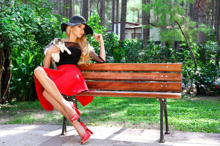 Beautiful elegant woman in a fashionable outfit and red hat posing on the background of the nature. Woman with cat.