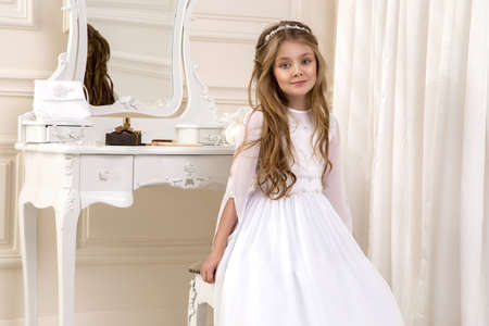 Little girl in white communion dress. First holy communion - concept. Young model in the white communion dress stands in an elegant palace.