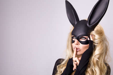 Sexy blonde beautiful woman posing in black bunny mask on white background. Easter bunny concept.