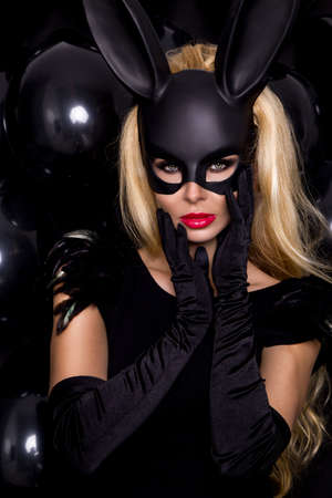 Sexy woman in a black bunny mask on blac balloons background. Masquerade. Sexy Girl in mask. Party.