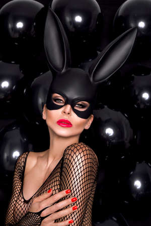 Beautiful Blond Woman in a Carnival Mask on balloons background. Sexy masked girl. Easter bunny.