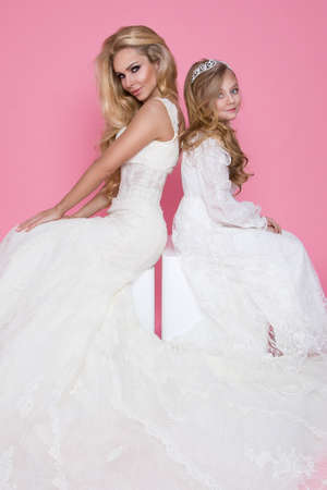 Wedding fashion. Beautiful bride and bridesmaid posing on pink background. Mother and daughter in wedding day.