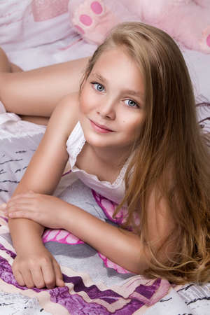 Cute little girl in pajama on the bed at home, happy childhood concept. Beautiful girl in bed.
