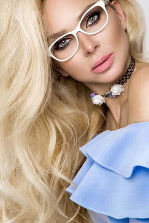 Blonde girl with long and shiny wavy hair wearing glasses. Beautiful model with a curly hairstyle and natural facial beauty advertises the optical store. Eyeglasses model - image