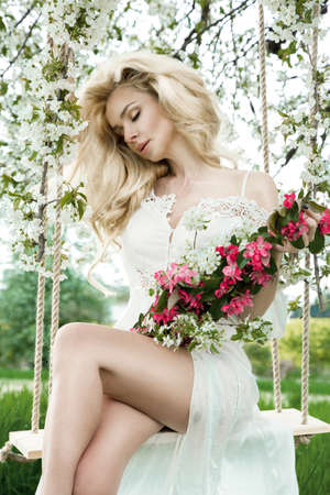 Beautiful happy and young woman enjoying smell in a flowering spring garden. Swing girl in summer day.