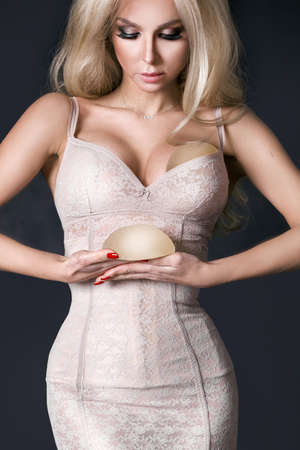Woman planning to have a implant. Silicone implants on hand and natural
