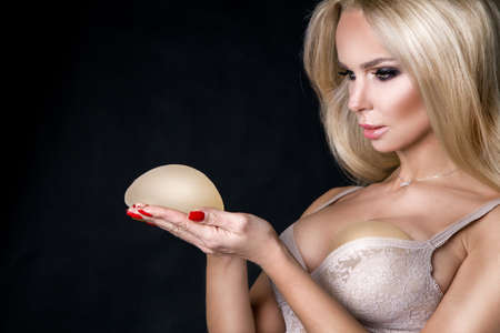Woman planning to have a implant. Silicone implants on hand and natural Stockfoto
