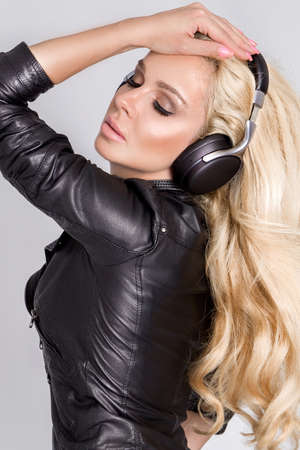 Beautiful young woman listening to music on headphones. Sexy girl listening music with her headphones in studio.