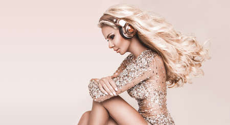 Beautiful young woman in headphones listening to music isolated on a beige background. Elegant girl in disco evening dress