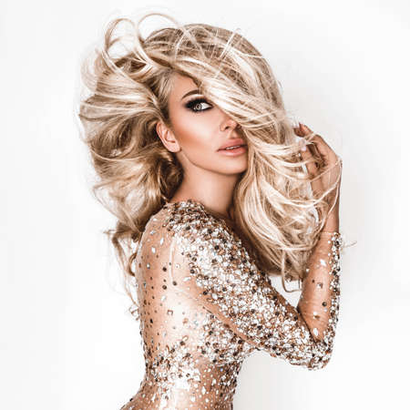 Blonde girl with long and shiny wavy hair. Beautiful model with curly hairstyle.