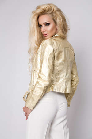 Beautiful model with long blond hair and leather gold jacket in the studio on a white background. Biker jacket. Gold fashion.