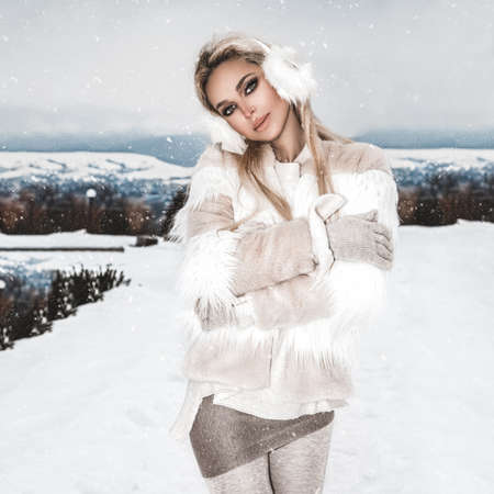 Young woman winter portrait. Winter fashion model. Attractive young woman in wintertime outdoor. Mountains, white snow in magic winter day.