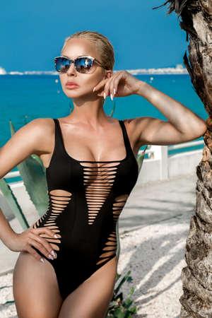 Sexy woman in elegant bikini and sunglasses in beach in Cannes France.