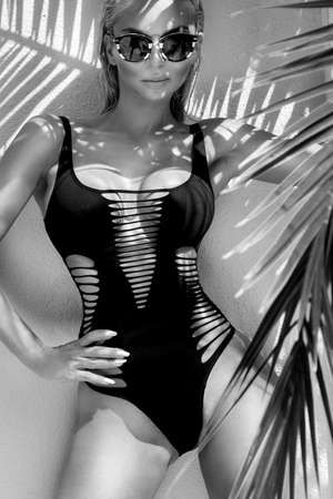 Sexy woman in elegant bikini on the sun-tanned slim and shapely body is posing near the palm trees in Cannes France. Bikini model - concept. Standard-Bild