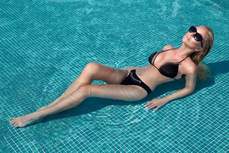 Sexy elegant woman in bikini in pool. Bikini and sunglasses fashion. Standard-Bild