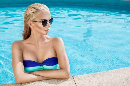 Sexy elegant woman in bikini in pool. Bikini hot model - concept. Bikini and sunglasses fashion. Standard-Bild
