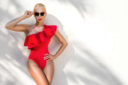 Sexy woman in red elegant bikini on the sun-tanned slim and shapely body is posing near the palm trees in Cannes France. Bikini model - concept. Elegance. Standard-Bild