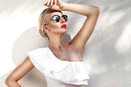Elegant sexy blonde model with perfect tanned body wearing a sunglasses and elegant white bikini on amazing view with palm tree shadow in Cannes, France. Bikini model concept. Elegance. Imagens