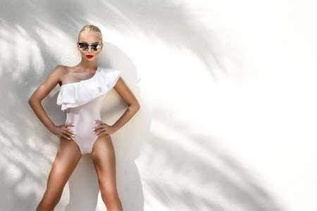 Elegant sexy blonde model with perfect tanned body wearing a sunglasses and elegant white bikini on amazing view with palm tree shadow in Cannes, France. Bikini model concept. Elegance. Standard-Bild