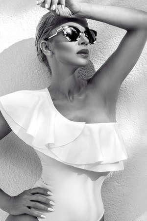 Elegant sexy blonde model in elegant white bikini on amazing view with palm tree shadow in Cannes, France. Bikini model concept. Elegance. Black and white photo. Standard-Bild