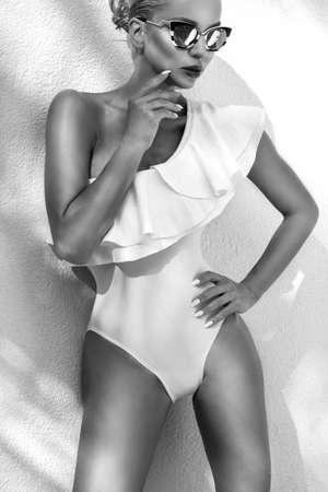 Elegant sexy blonde model in elegant white bikini on amazing view with palm tree shadow in Cannes, France. Bikini model concept. Elegance. Black and white photo. Imagens