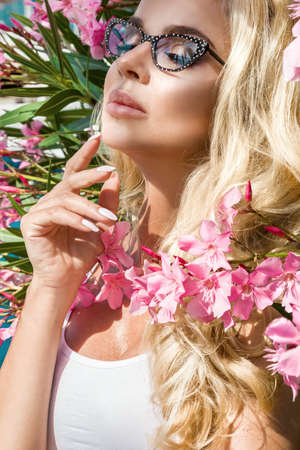 Beautiful elegant woman in eyeglasses on flowers background in Cannes France. Closeup portrait. Eyeglasses concept. Beauty face and makeup.