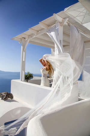 Romantic beautiful bride in white dress posing on terrace with sea and mountains in background. Bride in Santorini island. Bride, wedding concept.