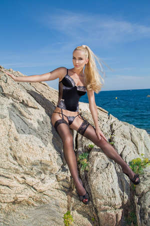 Sexy blonde model with lingerie and stockings on amazing view with sea and rocks in Spain. Hot lingerie model - concept. Stock Photo