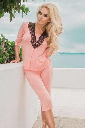Pajamas fashion. Beautiful blonde woman in pajamas near the sea landscape in luxury resort Stock Photo
