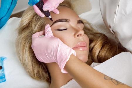 Permanent makeup treatment. Permanent makeup on eyebrows. Beautician making permanent makeup.