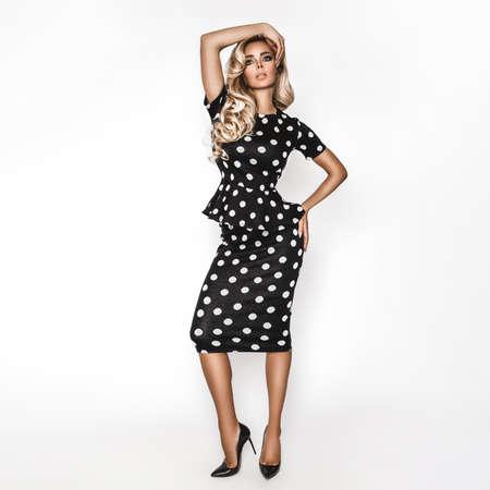 Fashion model dressed in elegant polka dot dress, isolated over white background. Spring fashion. Polka dots fashion - concept. Imagens