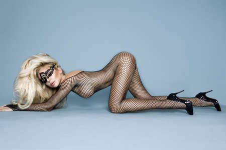 Sexy stunning blonde female model dressed in transparent bodystocking and sensual mask