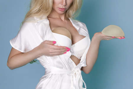 Breast implants. Woman planning to have a implant. Sexy blonde woman holds in her hands silicone implants, but has a natural breast.