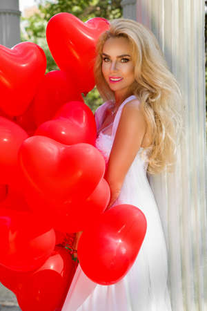 Bride in a wedding dress is walking in a beautiful garden and holding red balloons. Set of Air Balloons. Wedding fashion. Valentines day and bride at the wedding party. Stock Photo