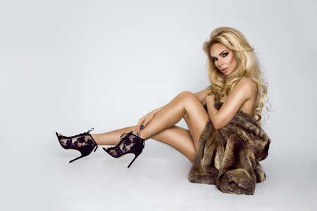 Fur fashion. Beautiful blonde model, dressed only in elegant fur. Gorgeous blonde woman posing in luxurious fur coat.