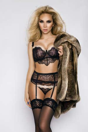Lingerie fashion. Sexy blonde female model in elegant lingerie and fur. Elegance.