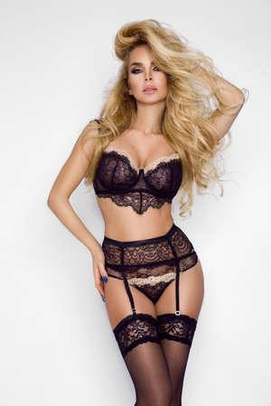 Lingerie fashion. Beautiful blonde woman in black elegant lingerie on a white background in studio. Hot model in lingerie. Foto de archivo