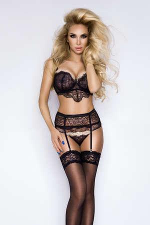 Lingerie fashion. Beautiful blonde woman in black elegant lingerie on a white background in studio. Hot model in lingerie.