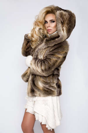 Winter fashion style. Beautiful woman In fur and jewelry. Portrait of young model in luxury fur coat and diamond earrings. High quality image. Banco de Imagens