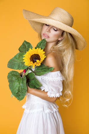 Spring fashion. Beautiful elegant woman in elegance yellow clothing and hat posing in studio on yellow pastel background. Natural beauty concept.