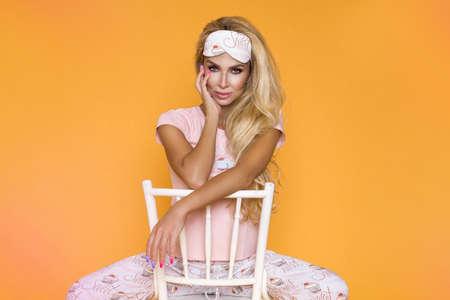Beautiful blonde woman in pajama on a yellow, pastel background in the studio. Sleepwear. Pajamas fashion. Fashion shooting concept.